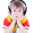 Stock Photo: Portrait of a sweet young boy listening to music on headphones