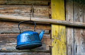 Old lost broken kettle on wooden wall — Stock Photo