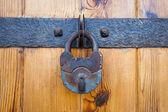 Rezavého visacího zámku na staré dřevěné dveře — Stock fotografie