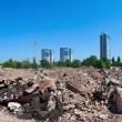 Stock Photo: Pile of debris of ruined building on new buildings background