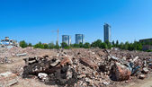Pile of debris of ruined building on new buildings background — Stock Photo