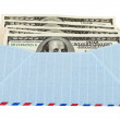 Stock Photo: US dollars in airmail envelope isolated on white background.