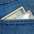 U.S. dollars and condom in the back jeans pocket — Stock Photo