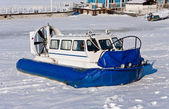 Hovercraft crossing frozen river against a blue sky — Stock Photo