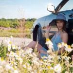 Beautiful brunette woman sitting near car — Stock Photo