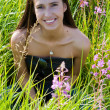 Beautiful brunette woman in grass — Stock Photo