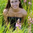 Beautiful brunette woman in grass — Stock Photo