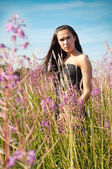 Woman standing in grass and flowers — Stock Photo