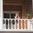 Royalty-Free Stock Photo: The woman on the balcony of a log cabin
