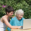 Foto Stock: Grandmother and granddaughter with laptop