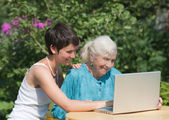 Grandmother and granddaughter with laptop — Stock Photo
