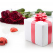 A bouquet of roses and a romantic gift on white background. — Stock Photo #8643646