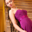 Woman in a beautiful dress sloit on the stairs — Stock Photo