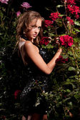 Woman standing among the rose bushes — Stock Photo