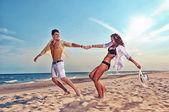 Boy and girl running on beach — Stock Photo