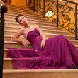 Woman in a long dress lying on the stairs - Stock Photo