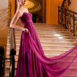 Woman in a beautiful dress sloit on the stairs - Stock Photo
