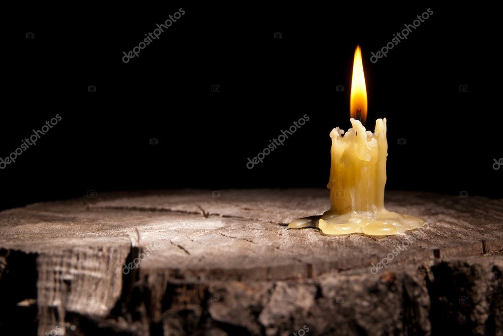 Old candle stands on the stump of a tree on the black background — Stock Photo #8100327