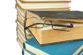 Pile of old books and glasses isolated on a white — Стоковое фото