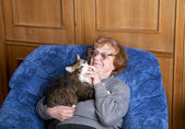 The old woman sits in an armchair and stroke a cat — Stock Photo