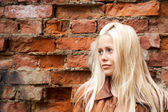 The girl blonde against an wall — Stock Photo