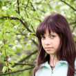 Girl teenager against a blossoming pear in the spring — Stock Photo