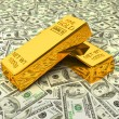 Gold bars on dollars — Stockfoto