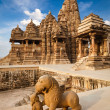 King and lion fight statue and Kandariya Mahadev temple - Foto de Stock  