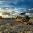 Long tail boat on beach on sunset - Stock Photo