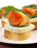 Canapes with smoked salmon cheese and cucumber — Stock Photo