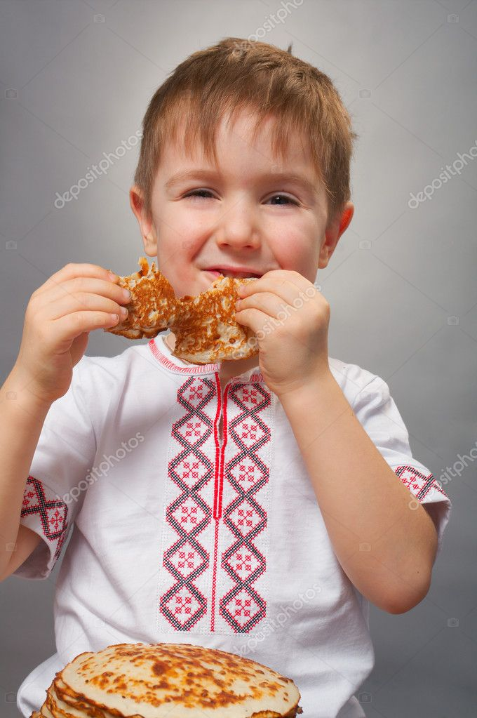 Russian little boy eats pancakes with red caviar.  Stock Photo #9239236