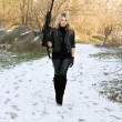 Beautiful young blonde with a gun - Stock Photo