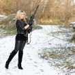 Beautiful young woman with a gun - Stock Photo
