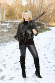 Sexy young blonde with a gun — Stock Photo