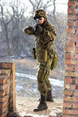 Soldier near wall with a gun — Stock Photo