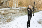 Nice young woman with a gun — Stock Photo