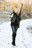 Perfect young woman with a gun — Stockfoto