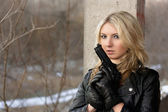 Scared young woman with a weapon — Stock Photo