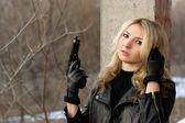 Confused blonde girl with a gun — Stock Photo