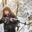 Brunette girl aiming a gun — Stock Photo
