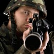 Ready soldier aiming a rifle in studio — Stock Photo