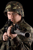 Watchful soldier aiming m16 in studio — Stockfoto