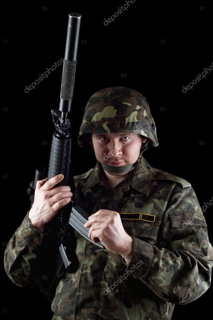 Soldier reloading magazine of m16 in studio. Isolated — Stock Photo #9786246