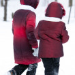 Girls leaves in a distance on snow — Stock Photo