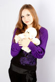 Beautiful young woman with a toy a monkey — Stock Photo