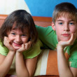 Stock Photo: Children lying on their bellies in bedroom