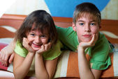 Children lying on their bellies in a bedroom — Stock Photo