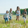Women with teens running in grass — Stock Photo