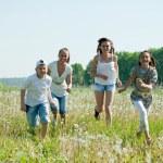 Women with teens running in grass — Stock Photo