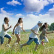 Women with teens running in grass — Stock Photo #10518837